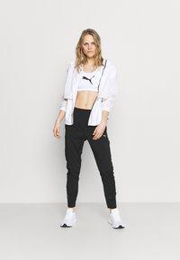 Puma - RUN TAPERED PANT - Pantalones deportivos - black - 1