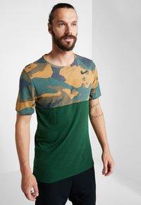 Nike Performance - DRY CAMO - T-shirt z nadrukiem - cosmic bonsai/team gold/black - 0