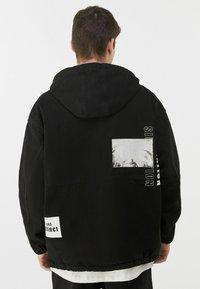 Bershka - MIT BAUCHTASCHE UND PRINT  - Veste en jean - black - 2