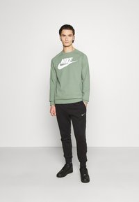 Nike Sportswear - REPEAT - Tracksuit bottoms - black - 1