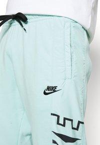 Nike Sportswear - Tracksuit bottoms - light dew/black - 5