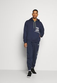 Puma - FRANCHISE - Tracksuit bottoms - peacoat