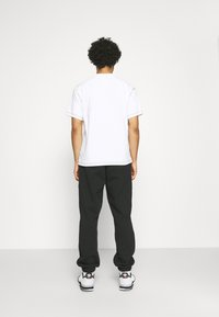 adidas Originals - BASICS UNISEX - Tracksuit bottoms - black - 2