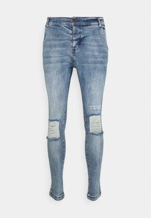 RAW HEM BURST KNEE - Jeans Skinny Fit - rustic blue wash