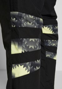 adidas Originals - FOOTBALL GRAPHIC TRACK PANTS - Verryttelyhousut - black - 3