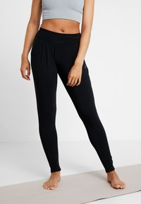 Curare Yogawear - PANTS LONG LOOSE ROLL DOWN - Tracksuit bottoms - black - 0