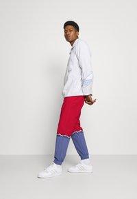 adidas Originals - SLICE TREFOIL ADICOLOR PRIMEGREEN ORIGINALS SLIM TRACK - Pantalones deportivos - scarlet/crew blue - 1