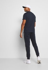 Champion - LEGACY  - Tracksuit bottoms - dark blue