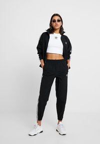 adidas Originals - LOCK UP ADICOLOR NYLON TRACK PANTS - Jogginghose - black - 1