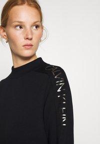 Calvin Klein - FUNNEL NECK LOGO DRESS - Shift dress - black - 4