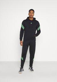 adidas Originals - SWAROVSKI HOODIE UNISEX - Luvtröja - black/shock lime - 1