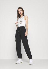 Nike Sportswear - CARGO PANT LOOSE - Teplákové kalhoty - black - 1