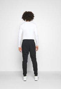 adidas Performance - DK ESSENTIALS - Tracksuit bottoms - black/white - 2