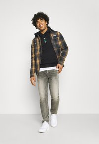 Calvin Klein Jeans - REPEAT TEXT GRAPHIC HOODIE UNISEX - Hoodie - black - 1