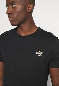 Alpha Industries - BASIC SMALL LOGO FOIL PRINT - Basic T-shirt - black/yellow gold - 5