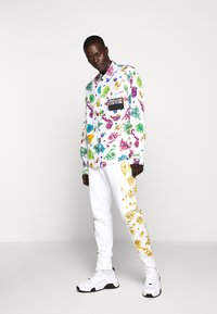 Versace Jeans Couture - JOGGERS GIOIELLI SIDE STRIPE - Tracksuit bottoms - white - 1