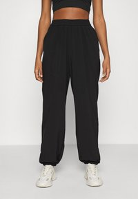 NA-KD - NA-KD X ZALANDO EXCLUSIVE - SPORTY FABRIC PANTS - Tracksuit bottoms - black - 0