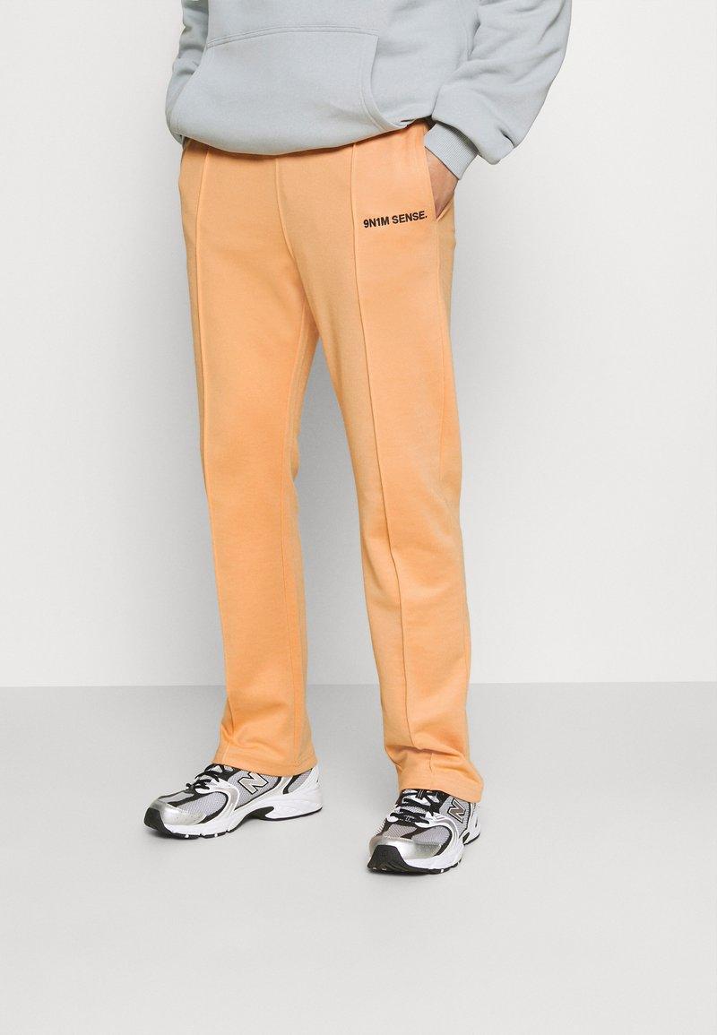 9N1M SENSE - LOGO PANTS UNISEX - Tracksuit bottoms - apricot/black