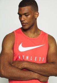Nike Performance - TANK ATHLETE - Sports shirt - track red - 4
