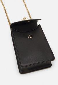 DKNY - ELISSA PHONE CBODY PEBBLE - Across body bag - black/gold - 4