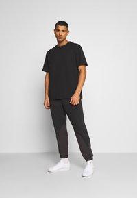 adidas Originals - UNISEX - Tracksuit bottoms - black - 1