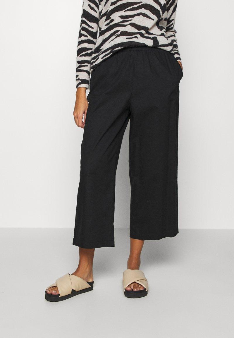 Monki - VILJA TROUSERS - Trousers - black dark