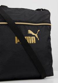 Puma - CORE SEASONAL SHOPPER - Tote bag - black/gold - 6