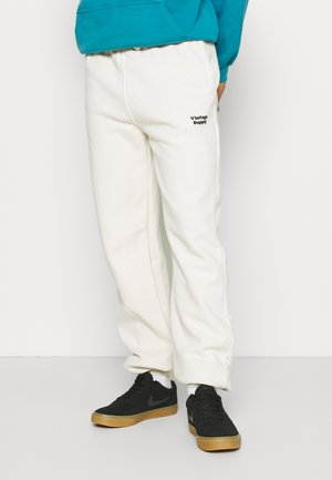 CORE OVERDYE  - Tracksuit bottoms - beige