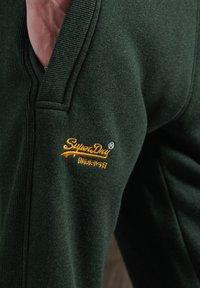 Superdry - ORANGE LABEL - Tracksuit bottoms - campus green grit - 0