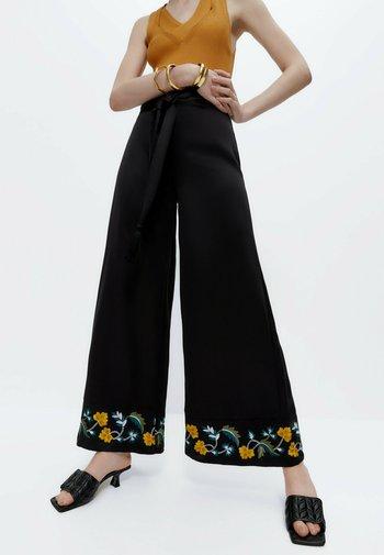 MIT STICKEREI - Trousers - black