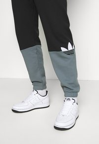 adidas Originals - SLICE - Tracksuit bottoms - black/blue oxide - 3