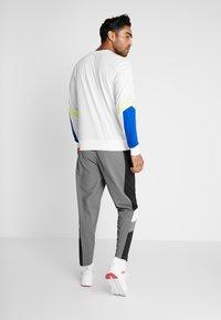 Puma - REACTIVE PACKABLE PANT - Outdoor trousers - castlerock black/white - 2