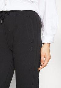 Calvin Klein Jeans - GLITTER MONOGRAM  - Tracksuit bottoms - black - 3