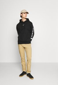 Nike Sportswear - REPEAT HOODIE  - Jersey con capucha - black/white - 1