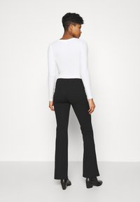 JDY - JDYCATIA FLARE - Trousers - black - 2