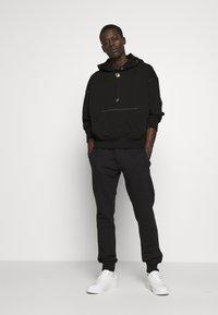 Versace Jeans Couture - BASIC JOGGERS - Tracksuit bottoms - black - 1