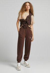 Bershka - MIT PRINT - Pantaloni sportivi - brown - 1