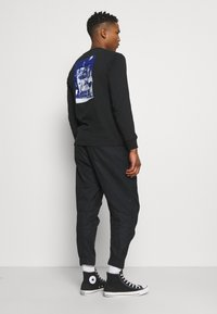 Converse - PANELED JOGGER - Cargo trousers - black - 2