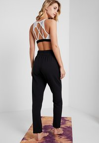 Nike Performance - FLOW PANT - Pantalon de survêtement - black/white - 2