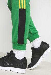 adidas Originals - CLASSICS  - Tracksuit bottoms - green/black - 6