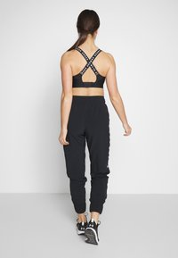 Under Armour - GRAPHIC PANTS - Tracksuit bottoms - black/onyx white - 2