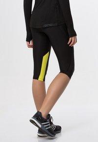 Skins - DNAMIC - 3/4 sports trousers - black/limoncello - 2