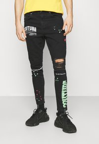 The Couture Club - NEON GRAFITTI CARROT FIT JEANS - Jeans slim fit - washed black - 0