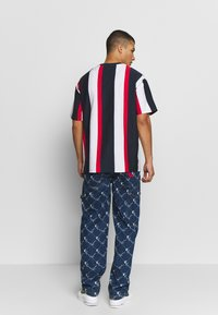 Karl Kani - UNISEX SIGNATURE STRIPE TEE - Print T-shirt - navy/red/white