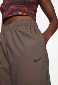 Nike Sportswear - Tracksuit bottoms - ironstone/black - 6