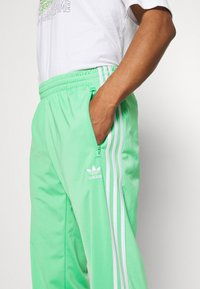 adidas Originals - FIREBIRD UNISEX - Spodnie treningowe - semi screaming green - 3