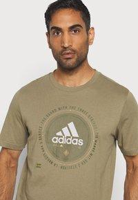 adidas Performance - UNIVERSAL - T-shirt med print - cargo - 4