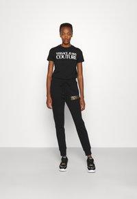 Versace Jeans Couture - PANTS - Tracksuit bottoms - black - 1