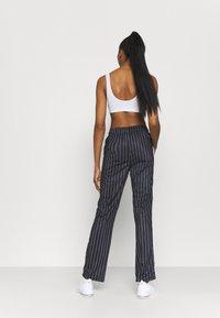 Fila - JAIMI PINSTRIPE TRACK PANTS - Teplákové kalhoty - black/bright white - 2