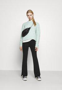 Monki - CASMIN FLARES - Trousers - black - 1